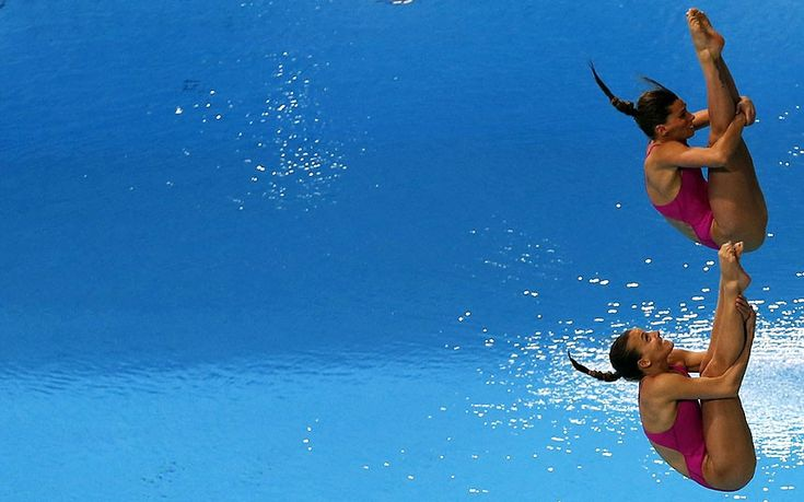 Tania Cagnotto and Francesca Dallape of Italy dive in the Women's 3M Synchro Springboard Final during the FINA/NVC Diving World Series 2014 at the Hamdan Sports Complex in Dubai