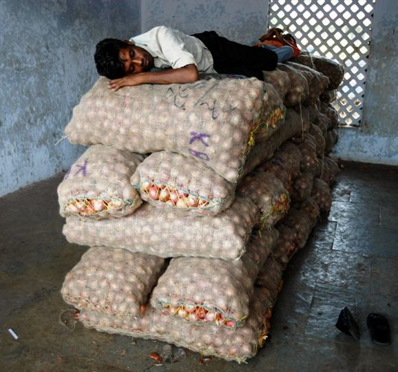 A trader sleeps on sacks of onions at a wholesale market in Ahmedabad.Amit Dave/Reuters