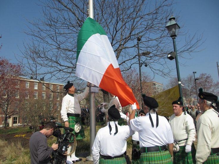 Hasteamento da bandeira da Irlanda, por participantes vestindo trajes típicos do país, no  Memorial irlandês em Filadélfia, Pensilvânia, USA.  Fotografia: Tom Keenan.