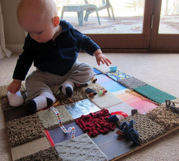 Texture sensory board for baby.  Made using free carpet and tile samples, paint chips, ribbons, etc.