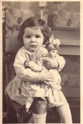 Vintage photo of cute little girl and her dolls.