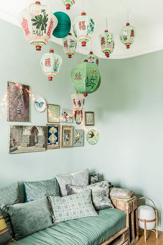 What a beautiful cozy nook! We love the Chinese paper lanterns in this green room with a cozy couch and lots of pillows.