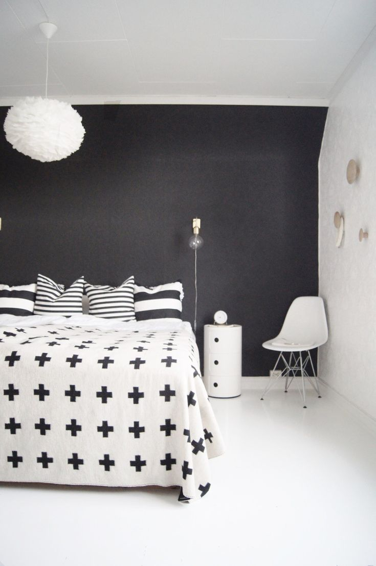 A bold black and white modern Scandinavian bedroom with simple, minimalist furniture. The same design could also work very well with dark blue.