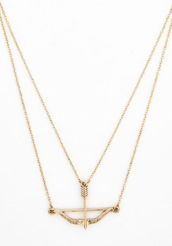 Signed, Sealed, and Quivered Necklace in Gold. When dressing up an outfit, you aim for on-target accessories such as this clever bow-and-arrow necklace - a ModCloth exclusive.  #modcloth