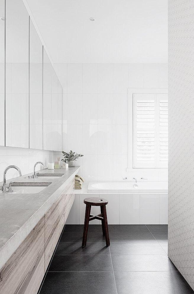 Jasne drewno w połączeniu z białymi płytkami o zróżnicowanej powierzchni, proste formy.