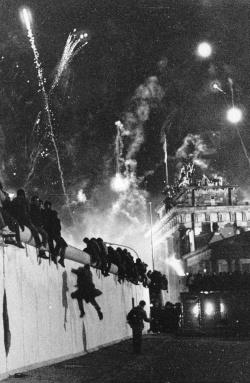 Foto: Menschen klettern über die Berliner Mauer - Die Mauer.  People climb over the Berlin Wall - The Wall