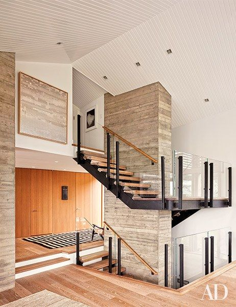 An artwork by Susan Noyes overlooks a glass, steel, and oak staircase | archdigest.com