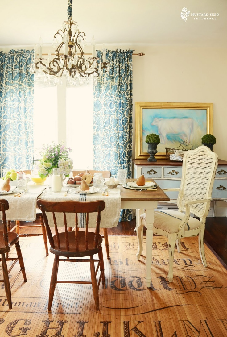 What a beautful room. I have to say, love the linen placemats. - and the cow, and the mis-matched chairs, curtains.