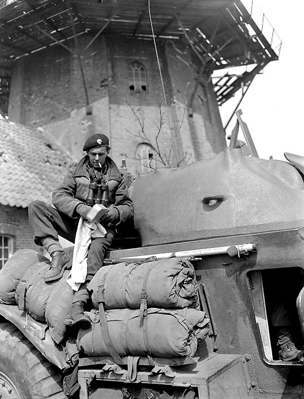 Sergeant I.F. Chase cleaning his mess tin on a General Motors T17E1 Staghound armoured car of the South Alberta Regiment, Bad Zwischenahn, Germany, 29 April 1945.