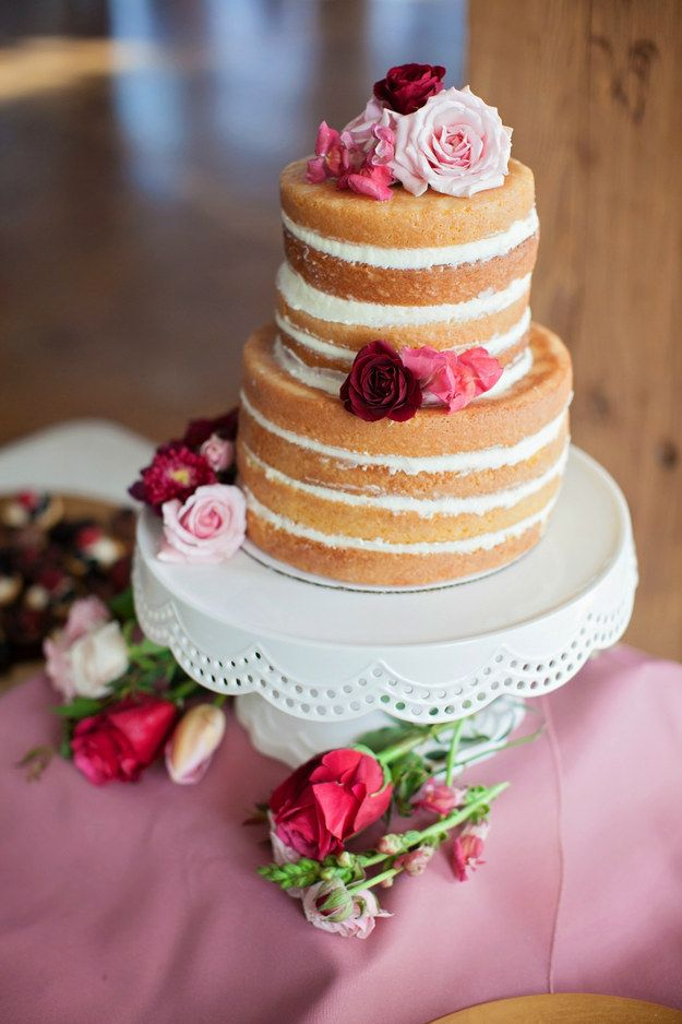 """A pretty """"naked"""" cake accessorized with roses."""