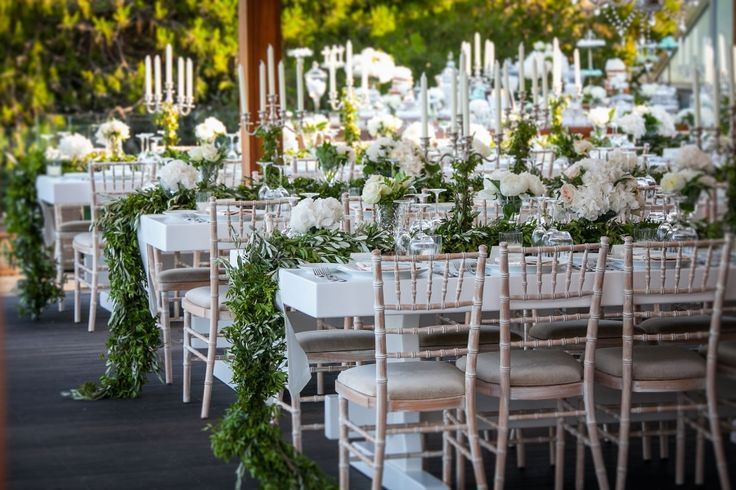 Amazing flower compositions on the wedding tables. Endless green garland made of olive branches spread along the table.