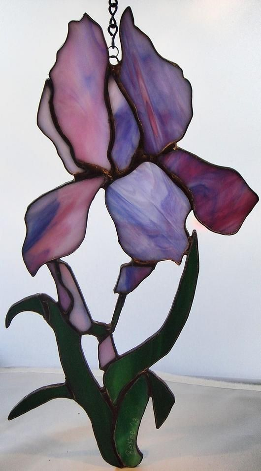"My Purple Iris In Spring - The glass is purple and white streaky opaque and green streaky opaque. The piece was made in the copper foil method. It was soldered, patina'd in black, and finished with a waxy coat of polish to shine and protect. It has a chain for hanging along with an 's' hook. It measures approximately 12""x 6""."