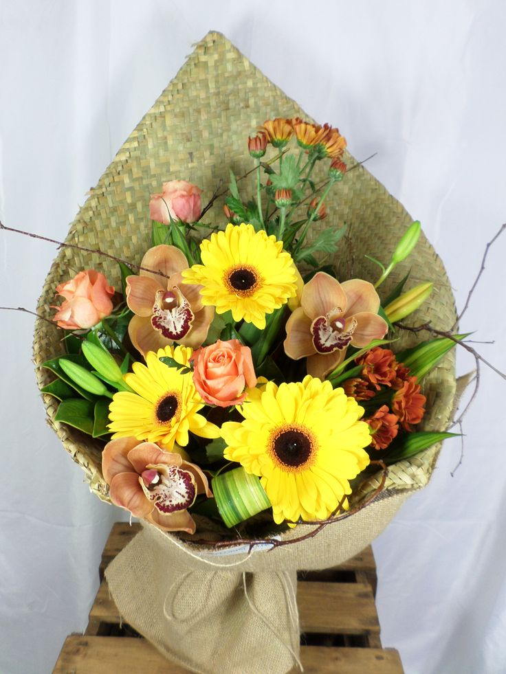 Flax wrapped bouquet with a lovely mix of gerberas and orchids. Created by Florist ilene