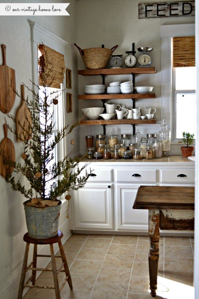 white and wood kitchen for Christmas with open shelving, white dishes, reclaimed wood, baskets, cutting board art, natural Christmas trees. Gorgeous!