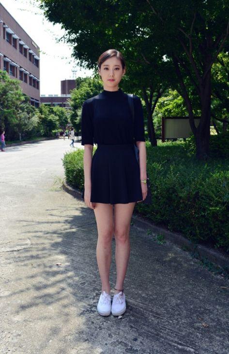 Half-sleeve mock turtleneck and a short skirt with light tennis shoes make for a dark, sleek, preppy look.,