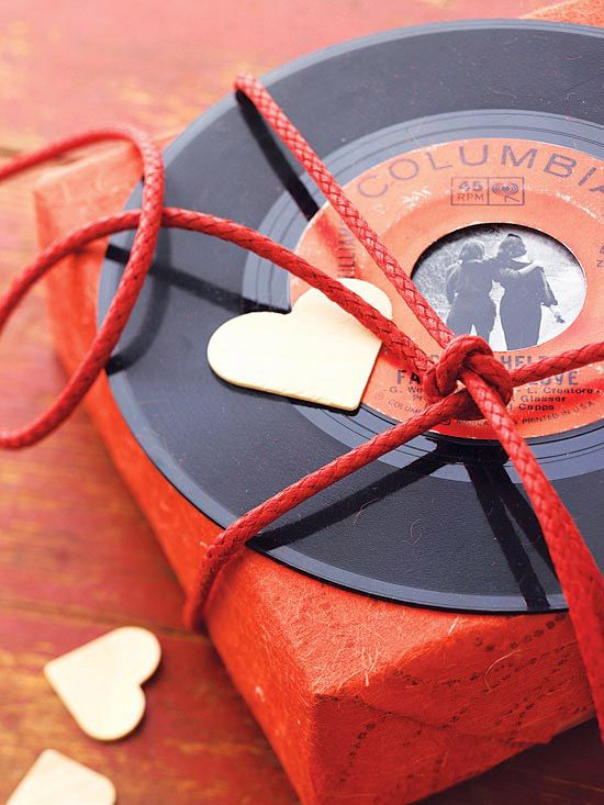 "record deal decoration -- browse thrift shops for 45s with special significance, such as Elvis singing ""Can't Help Falling in Love,"" to decorate a box of chocolates. Attach a personal photo to the back of the record with artist's tape before tying the vinyl in place"