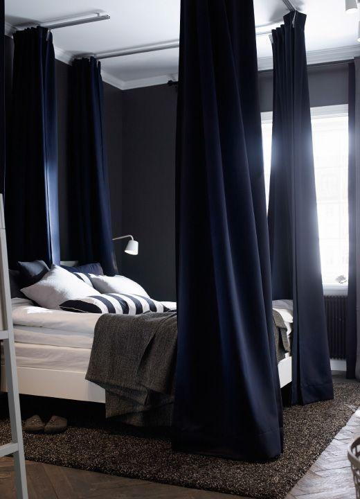 De donkerblauw geschilderde wanden van de slaapkamer en de frisse witte lakens op het bed helpen een gevoel van rust op te roepen. Gevoerde donkerblauwe gordijnen rond het bed en in het midden dempen licht en geluid. Een donkerbruin vloerkleed op de houten vloer voegt zachtheid en warmte toe.