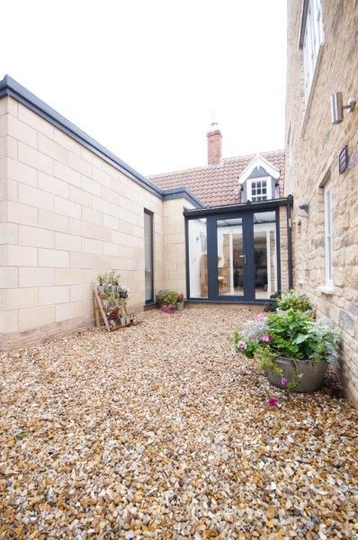 Front door and glass porch. Ashlar stone wall kitchen extension to left.