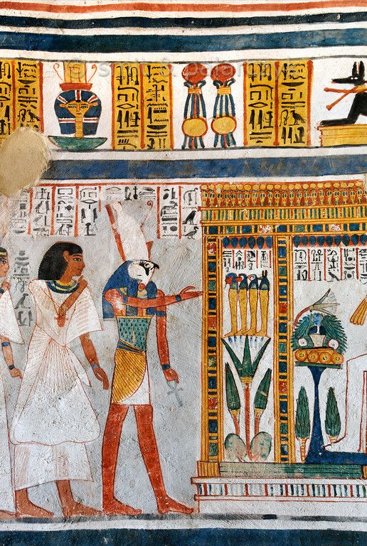[EGYPT 29381] 'Horus in Roy's tomb at Luxor.'  	A mural detail in the tomb of Roy shows Roy, in an attitude of deep respect, being led by Horus to a golden shrine in which Osiris presides (only his legs are visible here). Before Osiris stand the Four Sons of Horus: Amseti with the human head, Hapy with the baboon head, Duamutef with the falcon head and Qebehsenuef with the dog head. They are the guardians of the canopic jars which contain the internal organs of the deceased. They are…