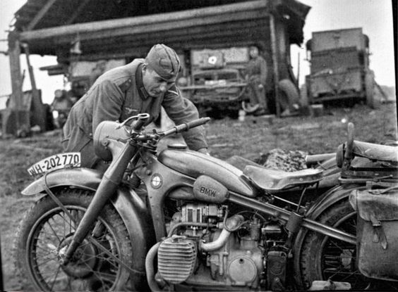 "A German soldier inspecting his BMW R12 motorcycle. Note the WH (""Wehrmacht Heer"") registration plate."