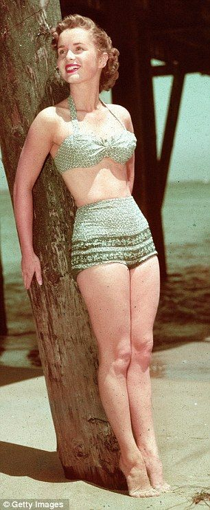 1955: Debbie Reynolds in a 2-piece bathing suit. 50s vintage fashions style color photo print ad movie star beach resort bikini blue green print