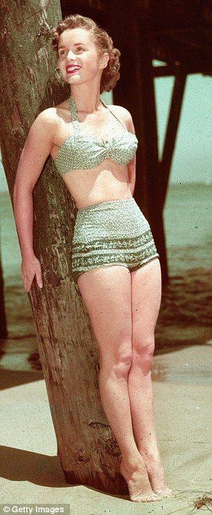 1955: Debbie Reynolds in a 2-piece bathing suit. 50s vintage fashions style color photo print ad movie star beach resort bikini blue green print