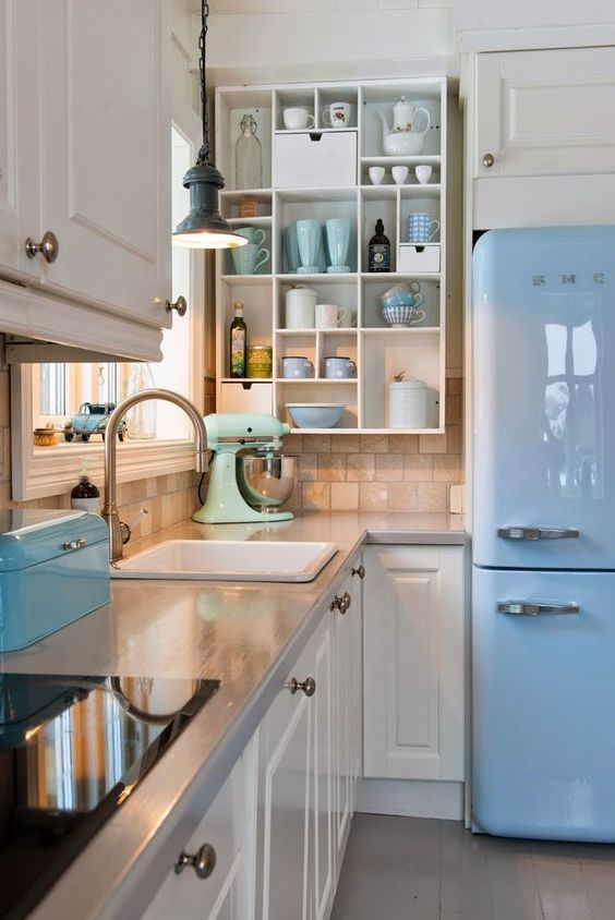 Freshen up cabinets with a splash of white, add open shelving and accents of pastel dishes and glasses, bread box, and an icy blue fridge for a vintage theme
