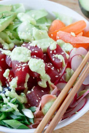 Get your sushi fix at home! This quick and easy tuna sushi bowl is packed with radishes, carrots, cucumber, seaweed and avocado then drizzled in a spicy avocado wasabi dressing.