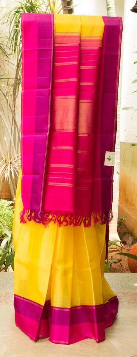 YELLOW kanchivaram kora silk WITH PINK AND PURPLE BORDER. THIN horizontal zari work on A GRAND PINK AND GOLD PALLU lends character to the piece.