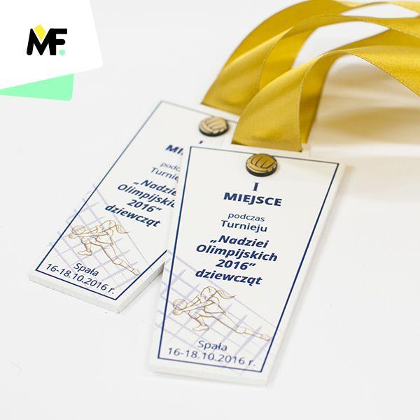 Medal o nieregularnym kształcie wykonany z białej pleksi z dodatkowym elementem z lamiantu w kolorze złotym. Teksturowany przestrzennie. Dwustronny medal przygotowany na zawody piłki siatkowej. Ozdobiony kolorową tasiemką. Wzór można dostosować do wytycznych klienta.
