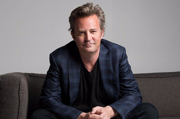 Matthew Perry sitting on a couch with his hands rested on his thighs