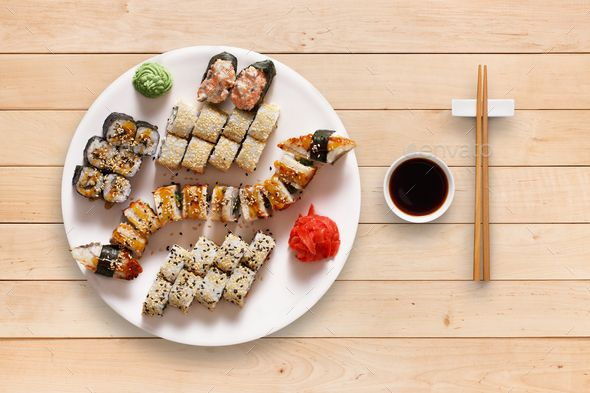 Set of sushi maki and rolls at black rustic wood. by Milkosx. Japanese food restaurant, unagi sushi maki gunkan roll plate or platter set. Set for two with chopsticks, ginger, soy...