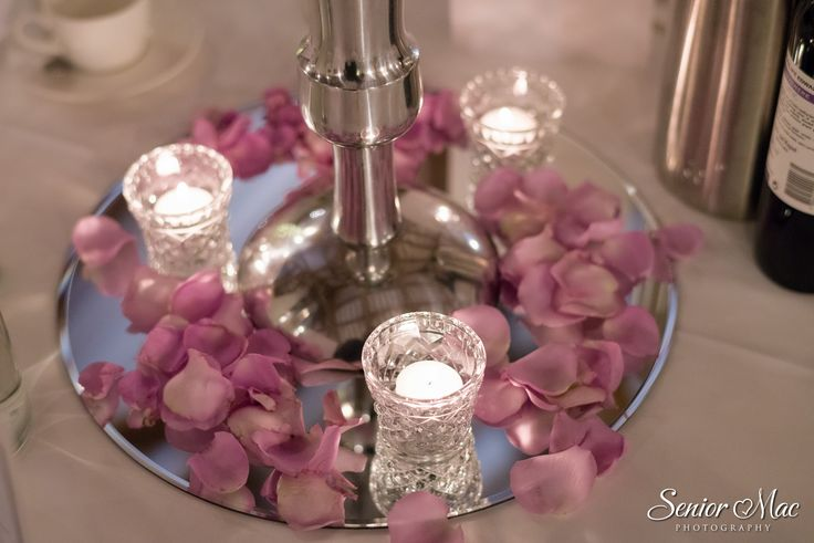 Mirror plates, cut glass tea light holders and plenty of rose petals at Rivervale Barn by www.tarniawilliams.co.uk