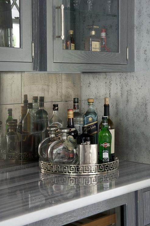 Amazing living room bar features glass front upper cabinets filled with glass shelves lined with glassware and gray wire brushed oak lower cabinets fitted with a glass front wine cooler paired with striped gray marble countertop and mirrored tile backsplash.