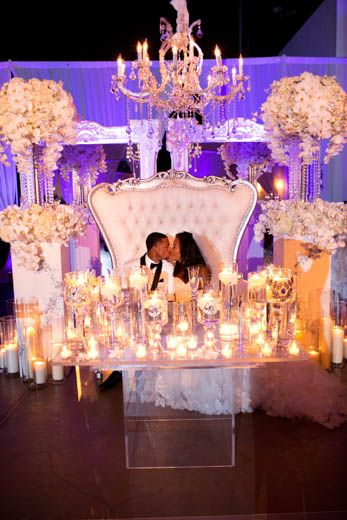 """BRIDAL BLISS: ASHLEY AND MELVIN'S NEW ORLEANS WEDDING DETAILS TO DIE FOR """"The sweetheart table was to die for,"""" says the bride. """"It was a mirrored table with tons of candles and flowers cascading off of the table, a huge sweetheart sofa, two very large flower arrangements, two more 10' white mirrors behind the sofa, and a chandelier hanging directly above us. There were lots of uplights and spotlights that set the ambiance of the room."""" By Charli Penn"""