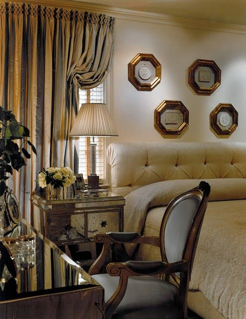 Awesome room ambiance: like the smokey mirrored nightstand,striped silk drapes  & tufted bed.  Replace the picture grouping - it isn't cutting it.