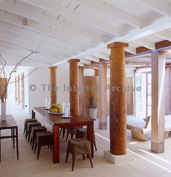 Rows of slip-covered French army stools line an oiled-assamela dining table which is separated from the entrance hall by rustic wooden columns made from old telephone poles