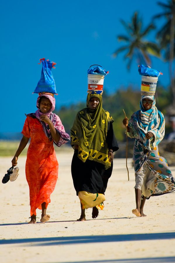 Three Local Women Walking on Kiwengwa Beach Zanzibar after a day's work harvesting seaweed.