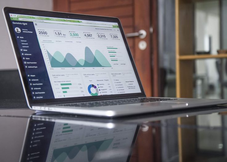 Charts with statistics on the screen of a laptop on a glossy surface