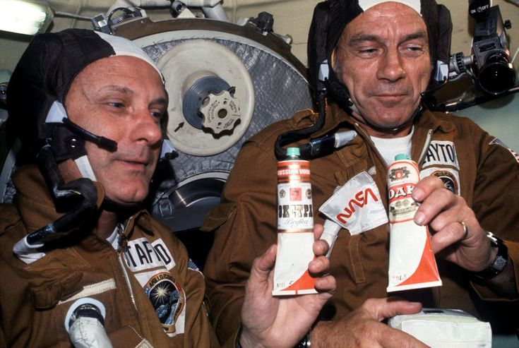 """(July 17, 1975) Astronauts Thomas P. Stafford (left) and Donald K. """"Deke"""" Slayton hold containers of Soviet space food in the Soyuz Orbital Module during the joint U.S.-USSR Apollo-Soyuz Test Project docking in Earth orbit mission. The containers hold borsch (beet soup) over which vodka labels have been pasted. This was the crews' way of toasting each other.  Image # : ast-003-175"""
