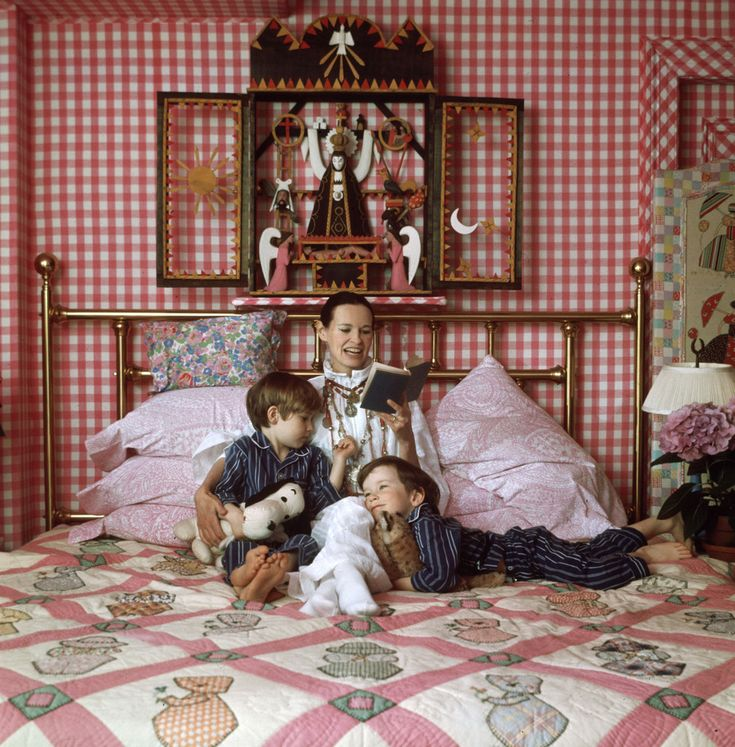 American heiress and socialite Gloria Vanderbilt reads to her two sons, Carter (1965 - 1988) and Anderson, on a bed in their home, Southampton, Long Island, New York, 1972. The children wear matching pajamas and hold stuffed animals. (Photo by Jack Robinson/Hulton Archive/Getty Images)
