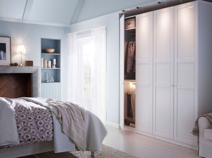 A white bedroom with a large wardrobe combination and a bed with bed textiles in white and beige.