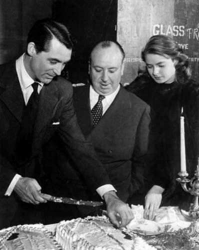 """Cary Grant, Alfred Hitchcock and Ingrid Bergman celebrate Cary Grant's birthday on the set of """"NOTORIOUS""""."""