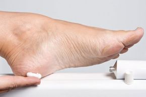 Smeer je voeten in met scheerschuim (de goedkoopste). Dompel een handdoekje in een badje van 1/2 warm water en 1/2 listerine (dat mondwater). Wikkel de handdoek om je (met scheerschuim ingesmeerde) voeten. Laat twintig minuten intrekken. Wrijf daarna met diezelfde handdoeken je voeten schoon. Je merkt dat er eelt en andere verharde huid meekomt. Afspoelen. En insmeren.