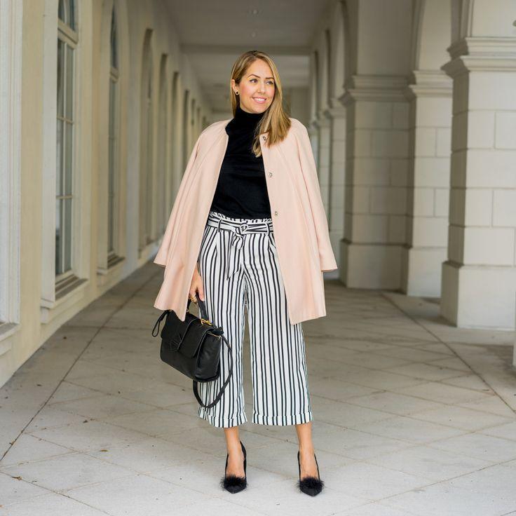 Розовое пальто, черный свитер с высоким ворот, полосатые брюки