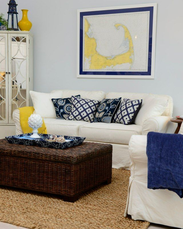 navy Yellow and white living room with a coastal flair. Sailcloth white slipcovered sofa nd love seat. A mix of blue patterned pillows and a framed $3. map of Cape Cod framed ties the whole look together. Natural jute rug and wicker storage ottoman add texture. nautical inspired accessories from @homegoods