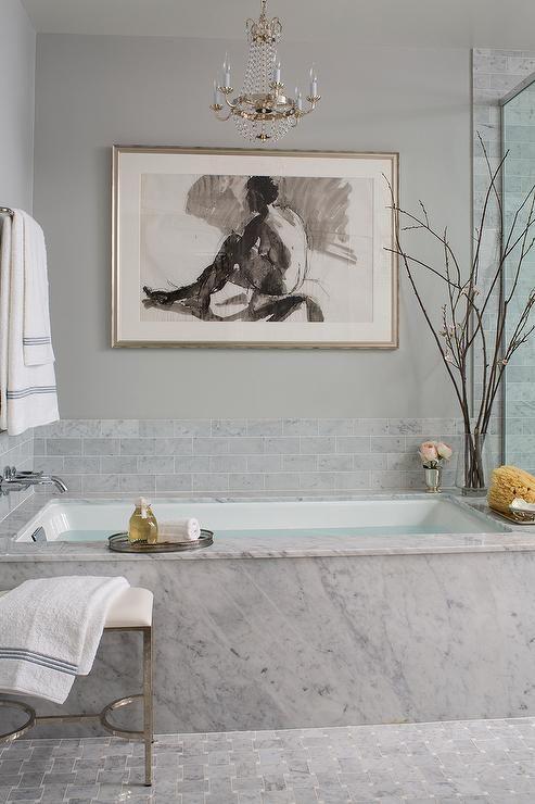 Spa like bathroom boasts a small Paris flea market chandelier hanging over a marble clad bathtub alongside a Waterworks Easton Metal/Vinyl Stool atop a gray marble geometrix tiled floor.