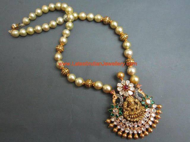 Beautiful Pearls and Nakshi Gold Balls Long chain with Temple Pendant Studded With Flat Diamonds, Diamonds, Rubys and Emeralds embossing Goddess Lakshmi with Peacock design on both sides. The pendant is lines with Tussi balls.