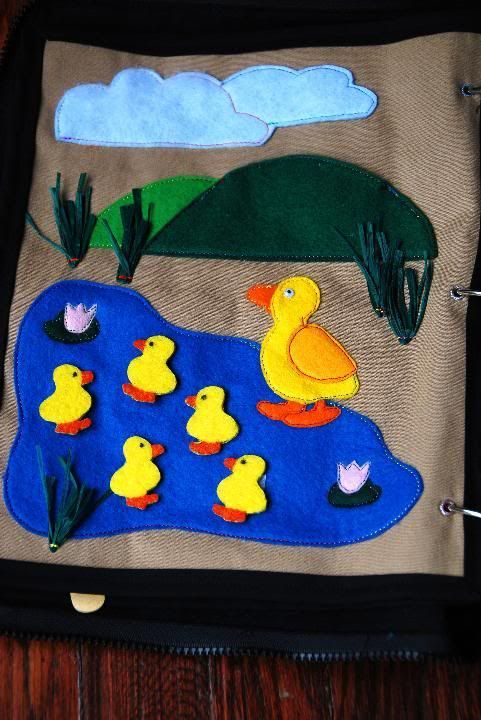 """The duck pond is perhaps my favorite page. I love the way it turned out. We sing, """"Five Little Ducks went out to play"""" and the ducks disappear behind the hill """"pocket"""". The reeds around the lake are made from green raffia (I knew there was a reason why I keep all my random craft supplies!)"""