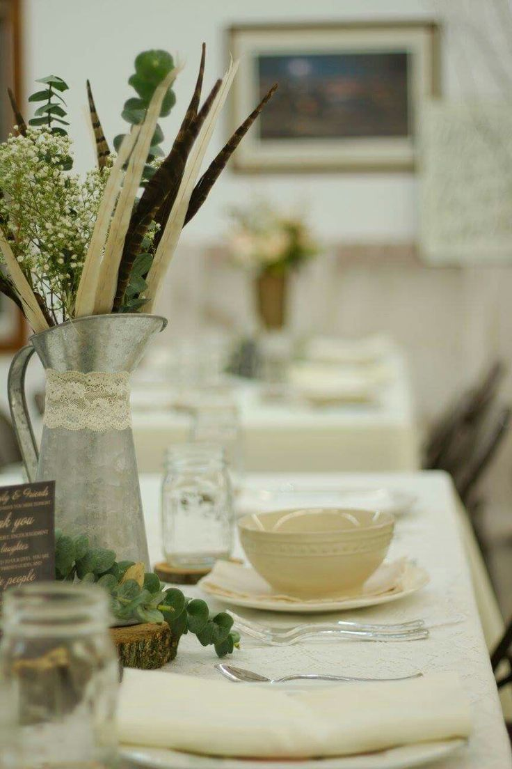 Centerpieces. Mismatched dishes. Metal pitcher. Lace. Feathers. Antlers. Baby's breath. Eucalyptus. Wood slab. Mason jars as glasses. Vintage Rustic Woodland Glam Boho Wedding reception